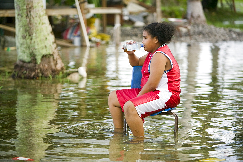 A teenage girl sits in the floodwater caused by sea water incursion due to global warming induced sea level rise that threatens the future of these low lying islands, Funafuti Atoll, Tuvalu, Pacific
