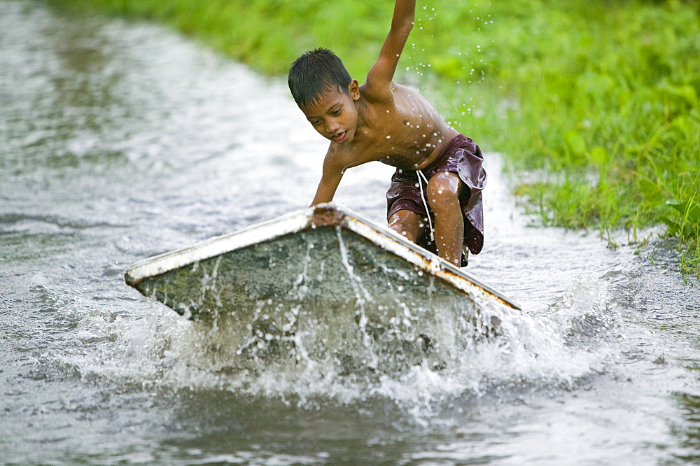 Boy playing in the floodwater caused by sea water incursion due to global warming induced sea level rise that threatens the future of these low lying islands, Funafuti Atoll, Tuvalu, Pacific - 911-1066