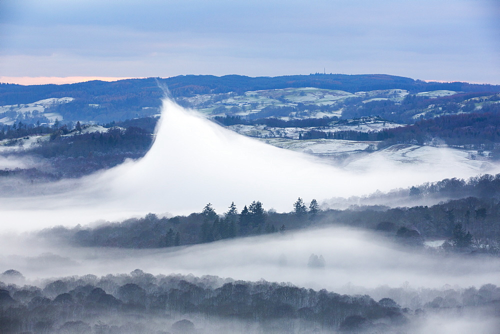 Looking down into the Langdale Valley above valley mist formed by a temperature inversion on Loughrigg, near Ambleside in the Lake District National Park. Localised warming has caused this very rare weather phenomenon, and lifted the mist up into a volcano shape.