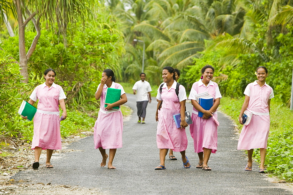 School girls walking home from school on Funafuti Atoll, Tuvalu, Pacific