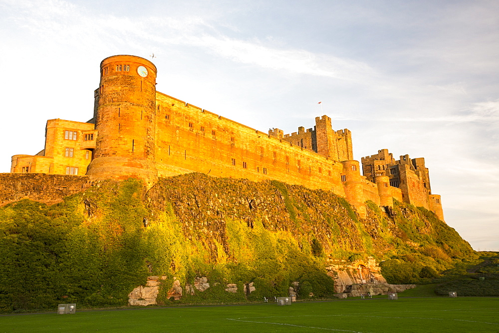 Bamburgh Castle, Northumberland, UK, in glowing light at sunset.