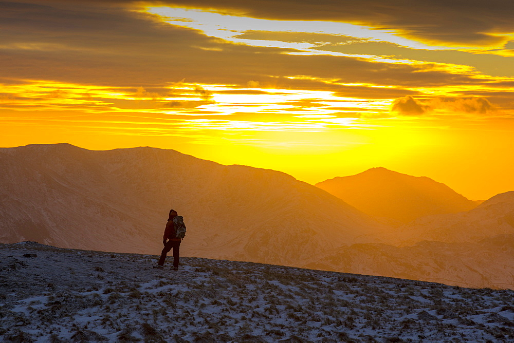 A walker on the summit of Red Screes at sunset in the Lake District, UK, taken on Wednesday 4th February 2015
