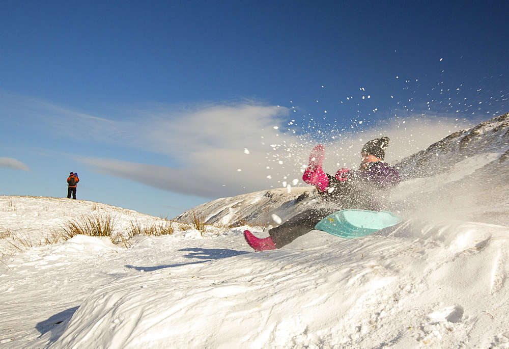A girl sledging on Kirsktone Pass in the Lake District, UK