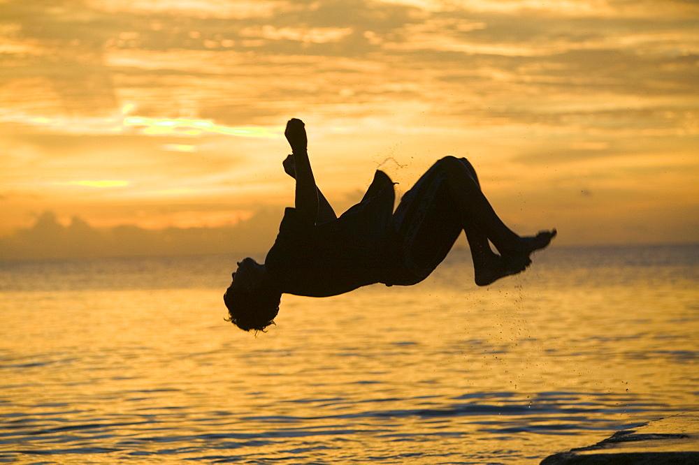 Tuvaluan children leaping into the sea on Funafuti Atoll, Tuvalu, Pacific