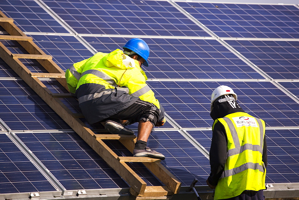Technicians work on Wymeswold Solar Farm the largest solar farm in the UK at 34 MWp, based on an old disused second world war airfield, Leicestershire, UK. It contains 130,000 panels and covers 150 acres.