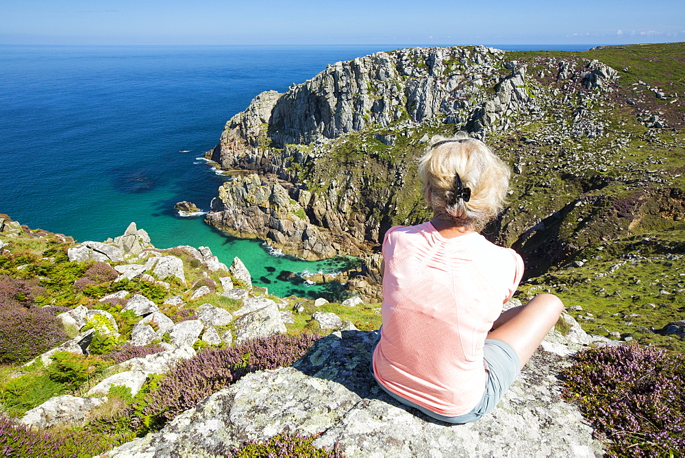 Granite sea cliffs at Bosigran on Cornwall's North Coast, UK, with a woman sat overlooking the sea.
