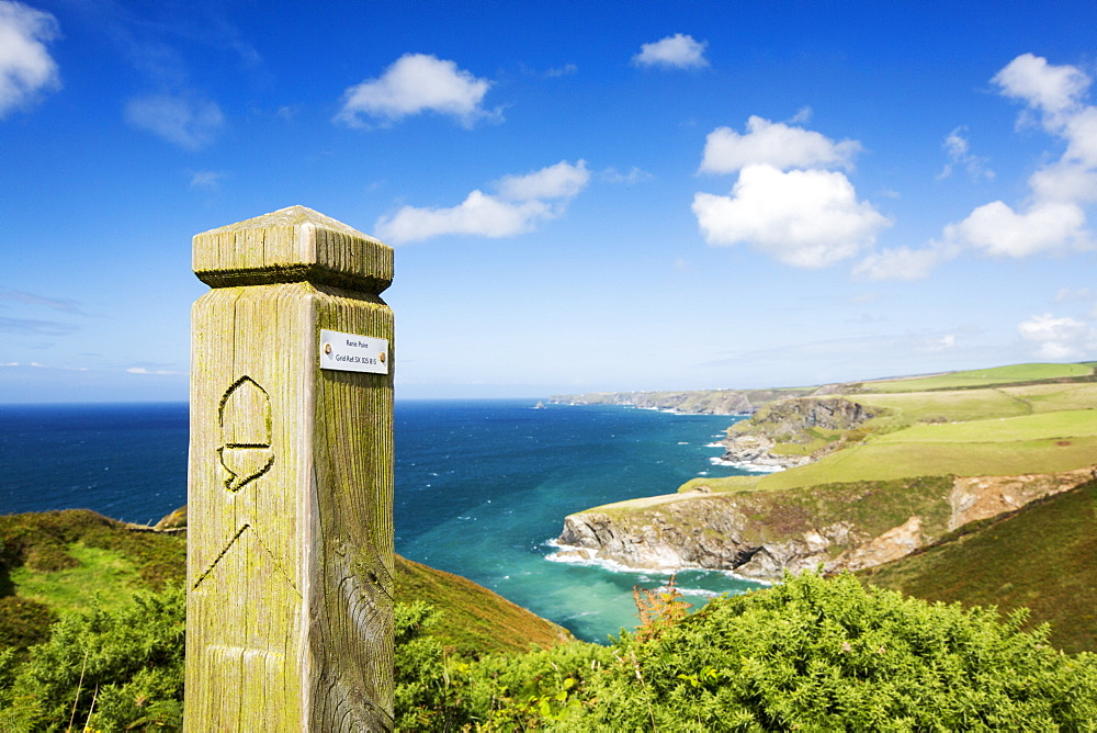 Coastal scenery on the South West Coast Path, East of Port Isaac, Cornwall, UK, with a path marker.