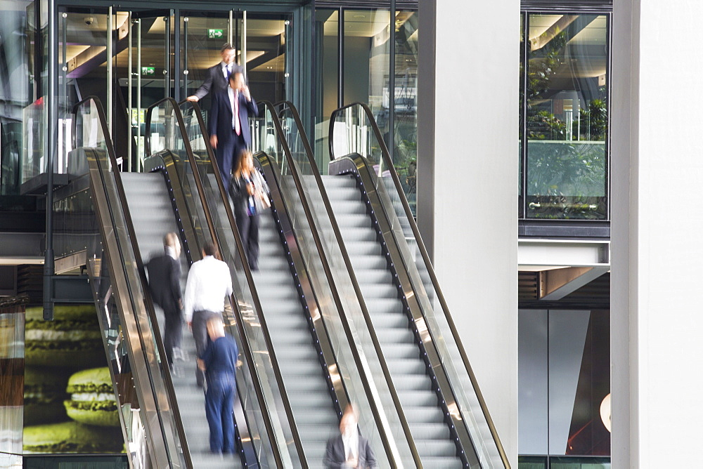 Workers entering and leaving the new Leadenhall building via escalator in the City of London, UK.
