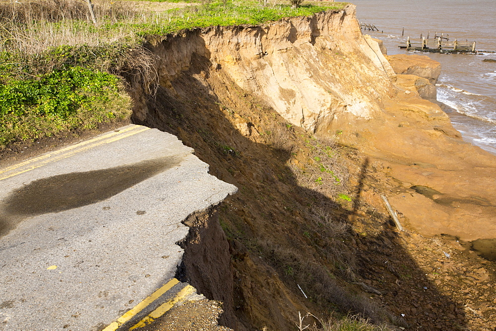 A road eroded and dropping off into the North sea at Happisburgh, Norfolk, a rapidly eroding section of coastline, UK.