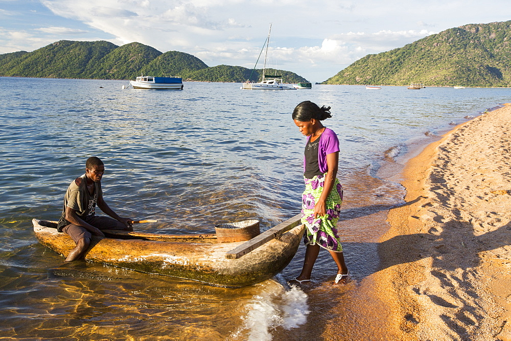 A fisherman in a traditional dug out canoe at Cape Maclear on the shores of Lake Malawi, Malawi, Africa. - 911-10914