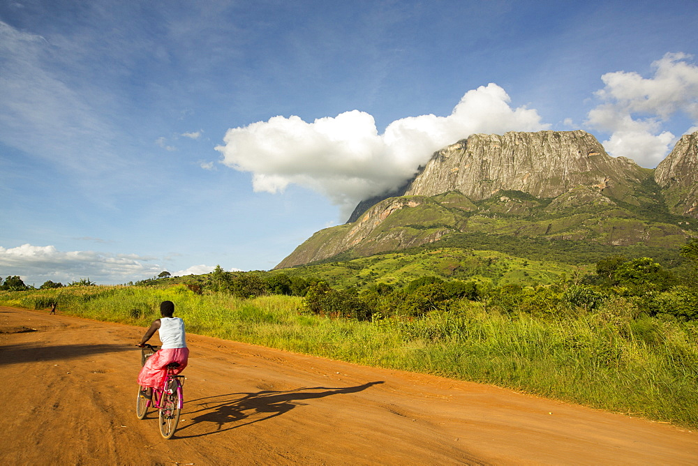A dirt track to Phalombe below Mount Mulanje in Malawi, Africa, with a woman on a bike.