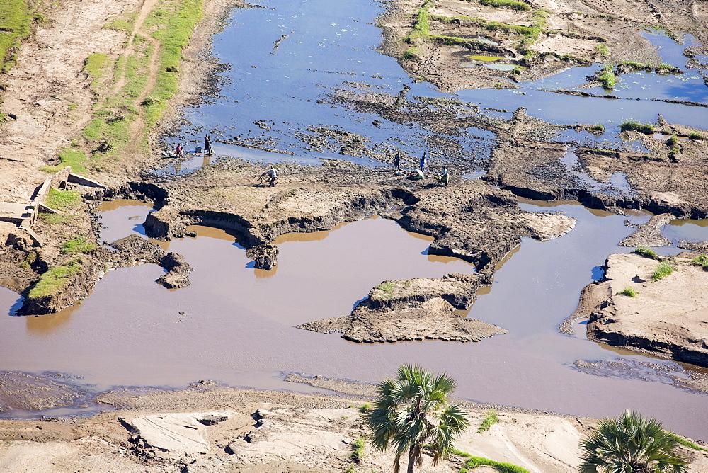 In mid January 2015, a three day period of excessive rain brought unprecedented floods to the small poor African country of Malawi. It displaced nearly quarter of a million people, devastated 64,000 hectares of land, and killed several hundred people. This shot taken from the air shows flood waters and farmland destroyed by the floods, with local farmers crossing their devastated fields.