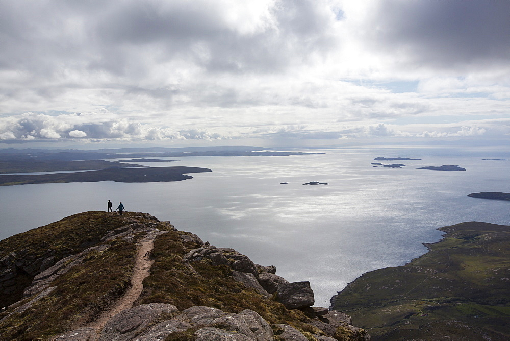 Walkers descending Ben Mor Coigach towards Loch Broom, looking towards the Summer Isles, Highlands, Scotland, UK.