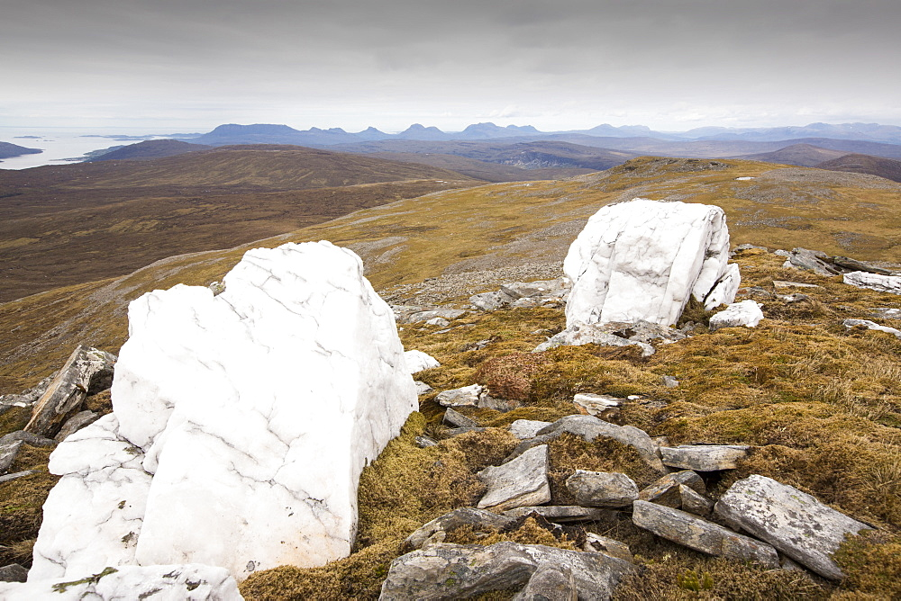 Looking towards the Assynt hills taken from  Eididh nan Clach Geala, Highlands, Scotland, UK, with large quartz boulders in the foreground.