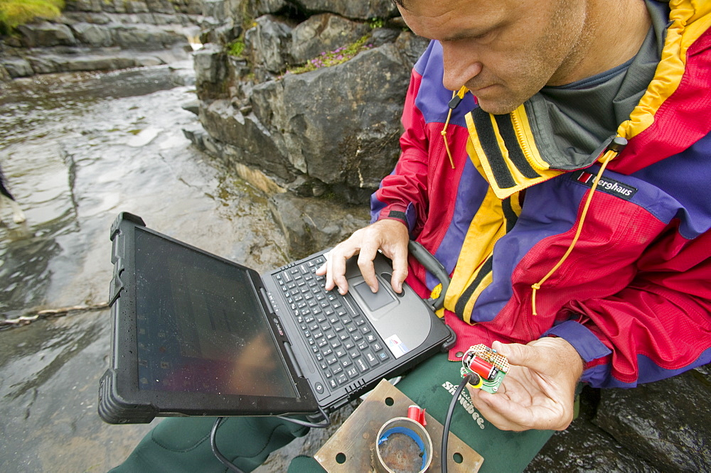 A scientist studying sediment load in a stream at Moorhouse in the north Pennines, Cumbria, England, United Kingdom, Europe - 911-1324
