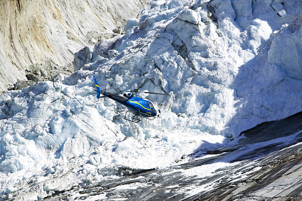 A tourist hericopter traverses melting seracs on the snout of the Argentiere Glacier, like most Alpine glaciers it is retreating rapidly due to global warming, Chamonix, Haute Savoie, France, Europe