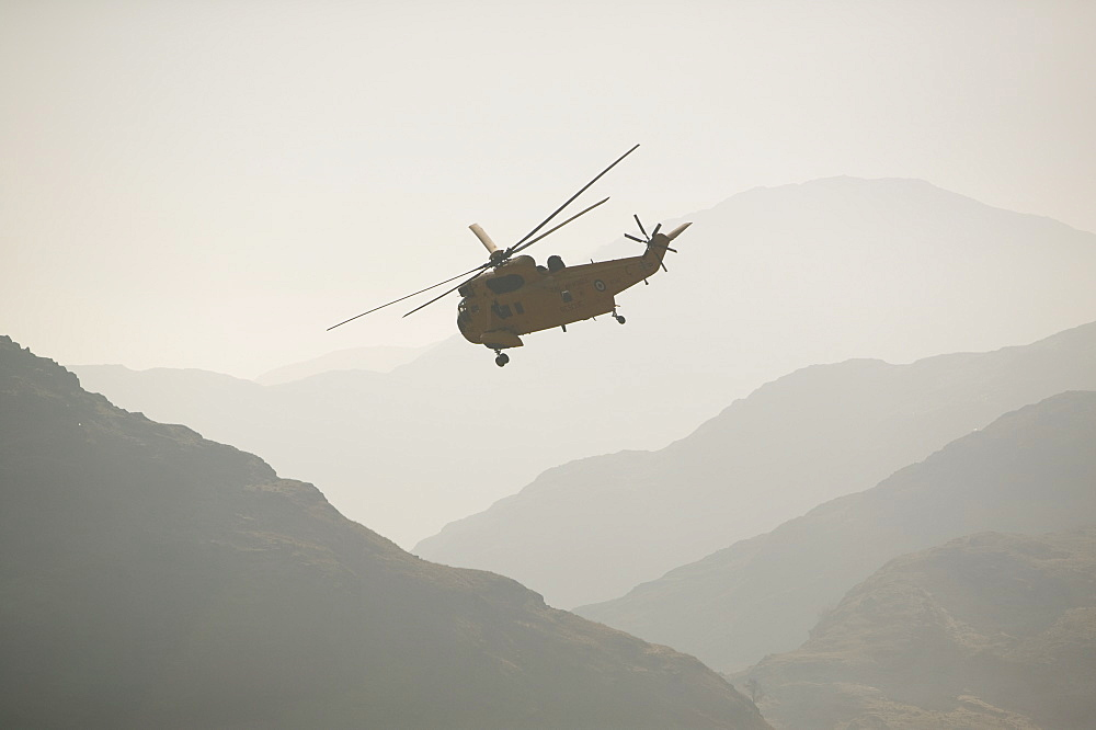 An RAF Sea King helicopter flying over the Langdale Valley in the Lake District, Cumbria, England, United Kingdom, Europe