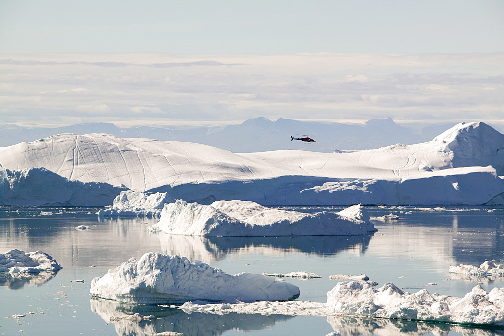An Air Greenland helicopter flies over the Jacobshavn Glacier (Sermeq Kujalleq) that drains Greenland's ice sheet Greenland, Polar Regions