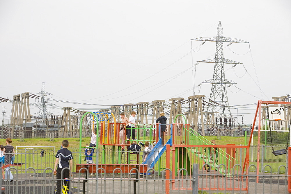 Children playing in front of an electricity plant and industrial complex in the town of Eston a suburb of Middlesbrough, Teesside, England, United Kingdom, Europe