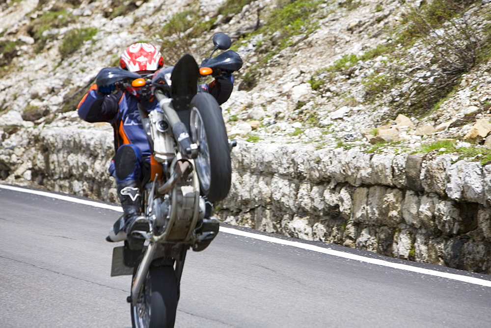 A motorcyclist showing off in the Italian Dolomites, Italy, Europe