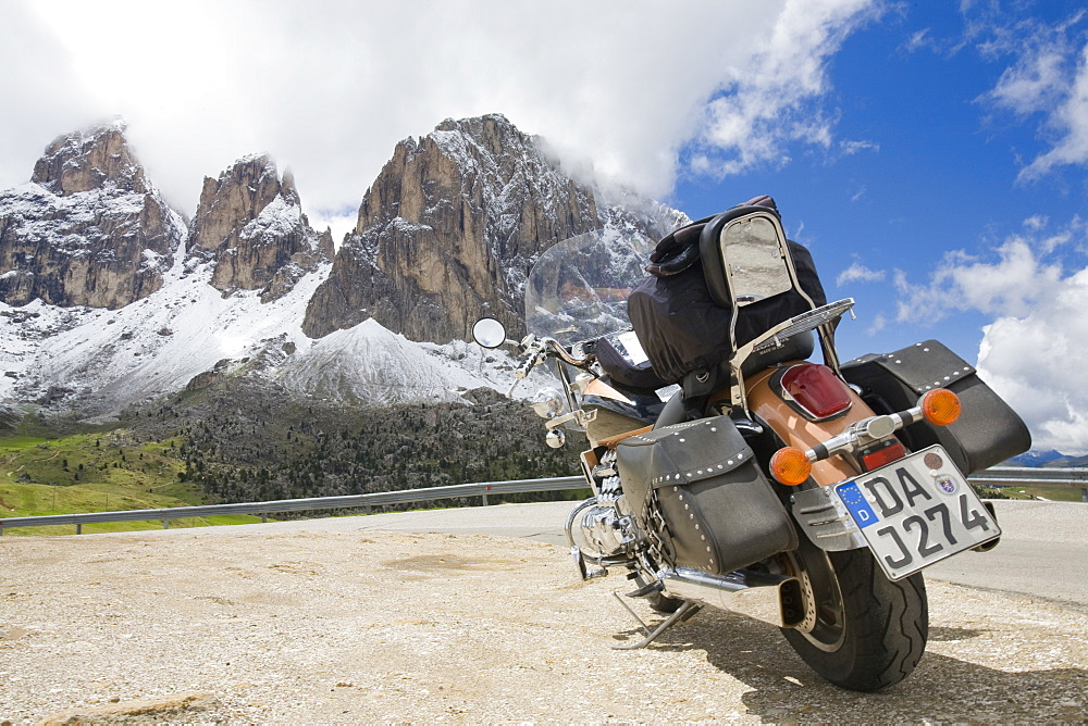 A motorbike on the summit of the Sella Joch pass in the Italian Dolomites with mountain view behind, Italy, Europe