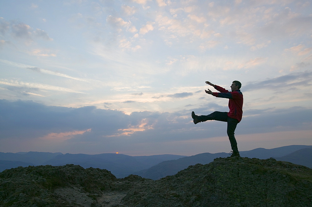 A man practising yoga moves in the mountains of the Lake District, Cumbria, England, United Kingdom, Europe