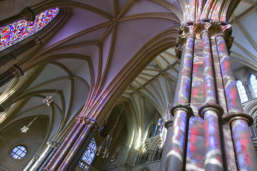 Light from stained glass windows on pillars in Lincoln Cathedral, Lincoln, Lincolnshire, England, United Kingdom, Europe