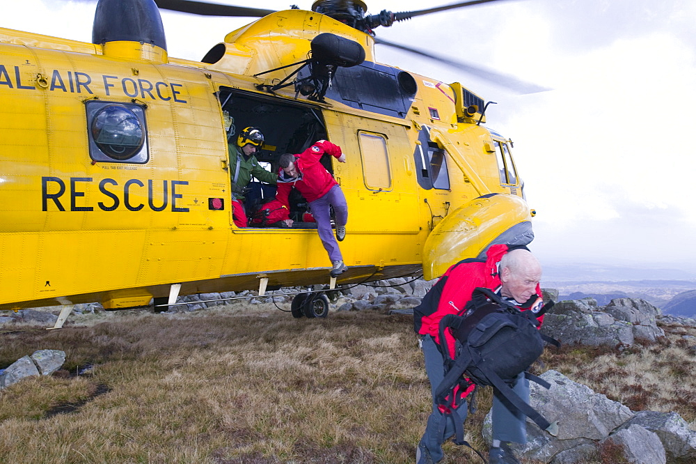 Mountain rescue team members and search dog handler with dog are dropped off by an RAF Sea King helicopter to start a mountain rescue search in the Lake District, Cumbria, England, United Kingdom, Europe