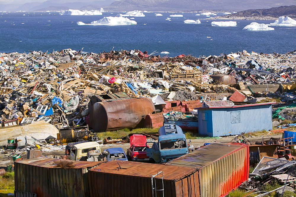 Rubbish dumped on the tundra outside Ilulissat in Greenland with icebergs behind from the Sermeq Kujalleq (Ilulissat Ice fjord), a UNESCO World Heritage Site, Greenland, Polar Regions - 911-292