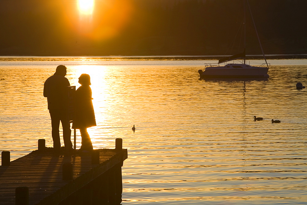 A couple on a jetty at sunset at Waterhead, Ambleside, Lake District, Cumbria, England, United Kingdom, Europe