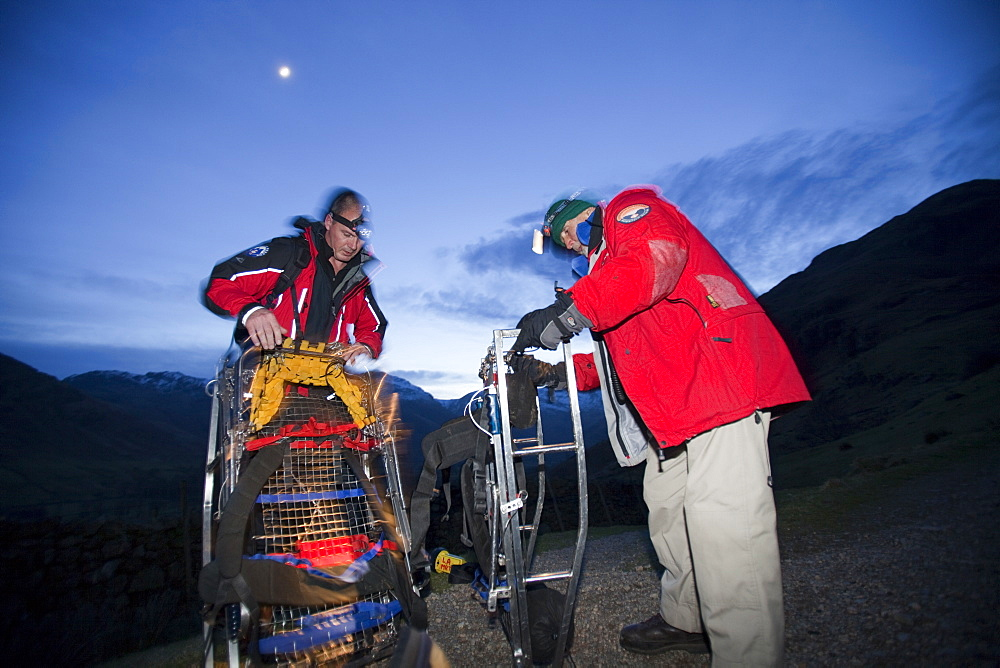 Langdale Ambleside mountain Rescue Team carry an injured walker off the Langdale Pikes at night near Ambleside, Lake District, Cumbria, England, United Kingdom, Europe