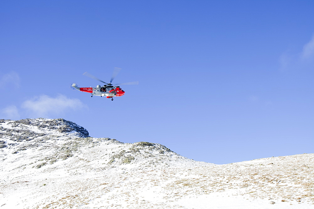 A Navy Sea King helicopter lowers a stretcher to evacuate a seriously injured walker who had fallen 250 feet on Bow Fell in the Lake District, Cumbria, England, United Kingdom, Europe