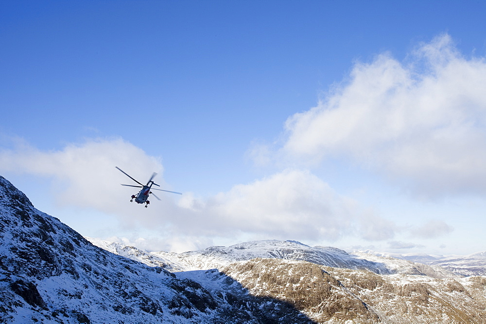 A Navy Sea King helicopter evacuates a seriously injured walker who had fallen 250 feet on Bow Fell in the Lake District, Cumbria, England, United Kingdom, Europe
