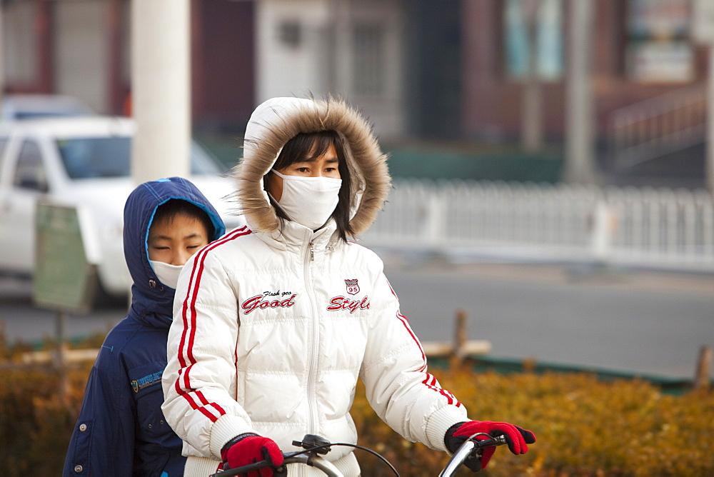 Cyclists in Beijing wearing smog masks to help protect against the awful air pollution, Beijing, China, Asia - 911-3836