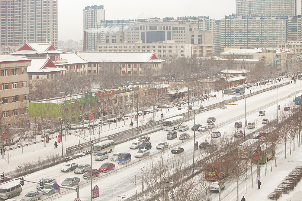 Cars in late winter snowfall in Harbin, Heilongjiang province, China, Asia