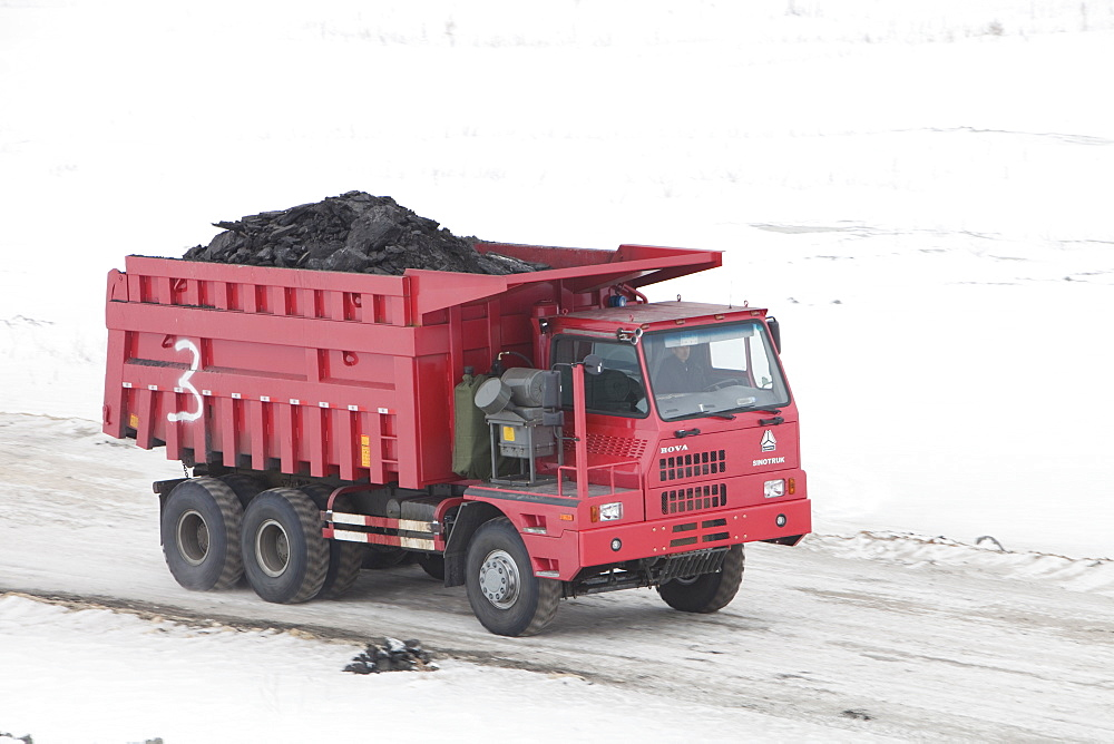 Trucks haul highly polluting low grade coal from an open cast coal mine near Heihe, Heilongjiang province on the Chinese Russian border, China, Asia
