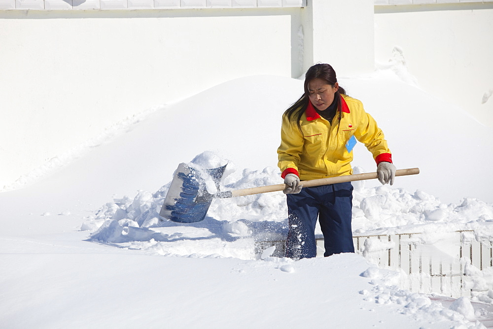 Workers in Heihe on the Chinese Russian border shovel heavy snow from the worst snowstorm to hit northern China in March for many years, Heilongjiang province, China, Asia