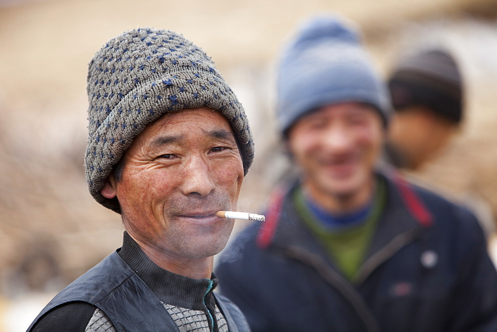 A chinese peasant famer smoking a cigarette in Heilongjiang province in Northern China, Asia
