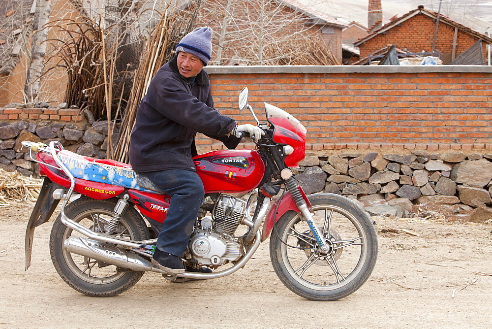 A Chinese man on a motorbike in Heilongjiang province in Norhern China, Asia
