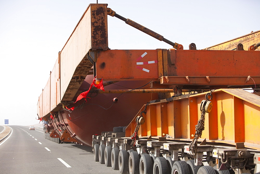 A huge load trundles on a low loader across Inner Mongolia, China, Asia