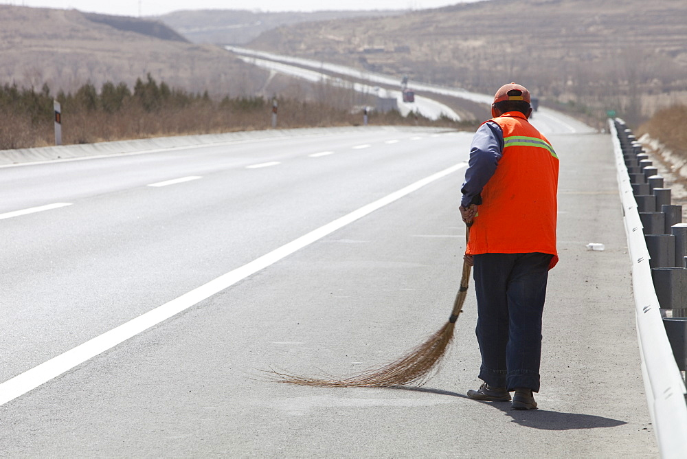A Chinese road sweeper sweeping the hard shoulder of the highway with a hand brush in Inner Mongolia, Northern China, Asia