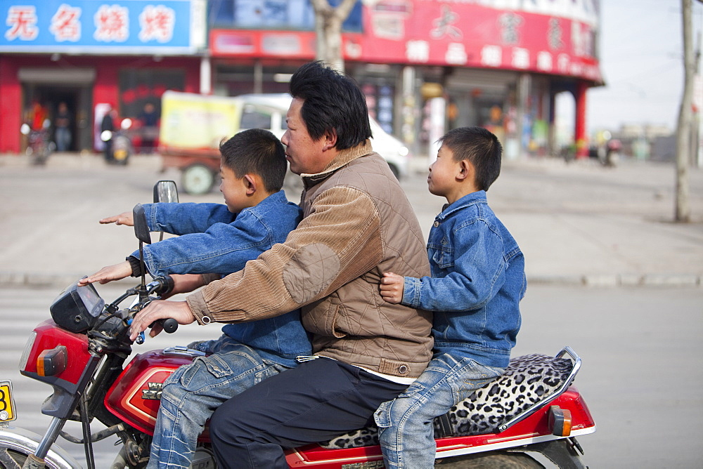 A father and two sons without crash helmets on a motorbike in Xian city, northern China, Asia