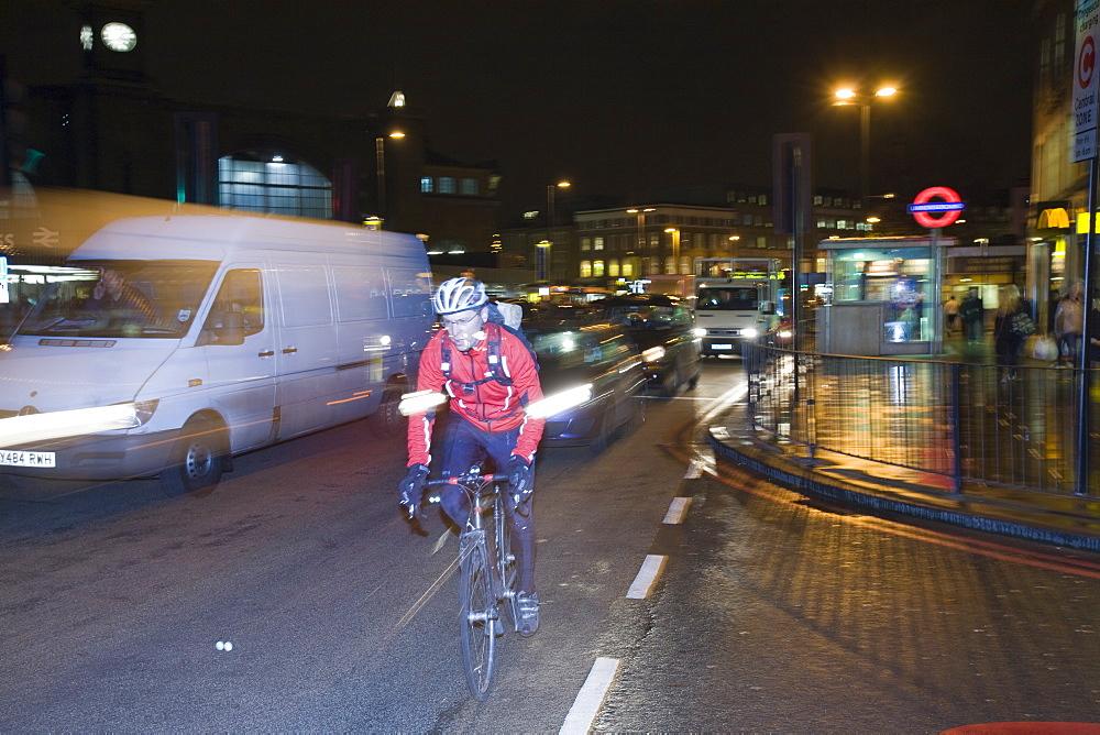 A cyclist at night outside Kings Cross, London, England, United Kingdom, Europe