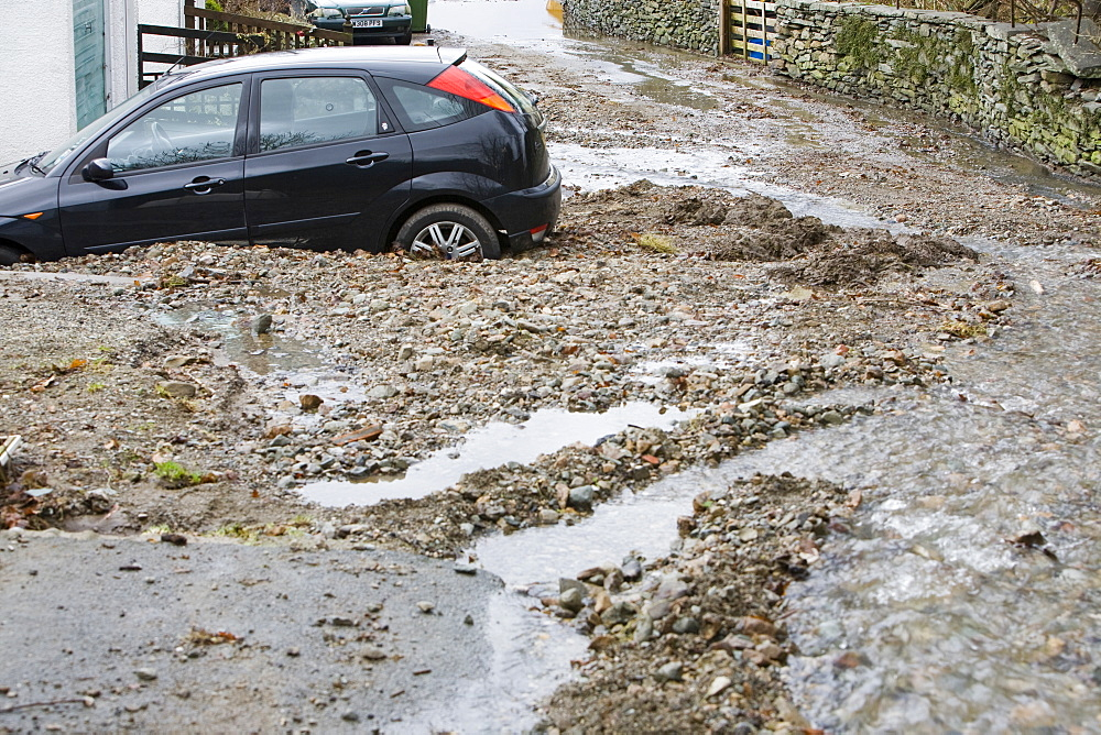 A car surrounded by flood debris caused by a flash flood in Ambleside, Cumbria, England, United Kingdom, Europe