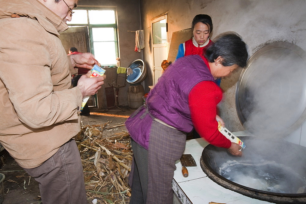A Chinese family cooks on a stove fuelled by dried corn stalks and husks which not only cooks the food and heats the water but also heats the house, Heilongjiang province, China, Asia