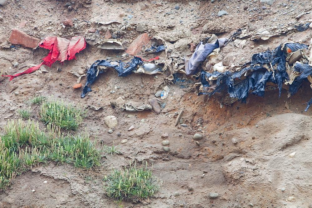Buried rubbish revealed by coastal erosion on the west coast of Walney Island, Cumbria, England, United Kingdom, Europe