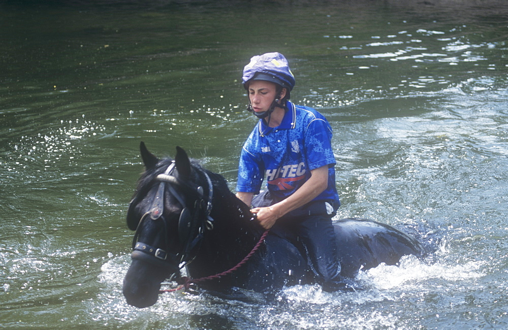 A gipsy man rides his horse through the River Eden at Appleby during the Appleby Horse Fair, Cumbria, England United Kingdom, Europe