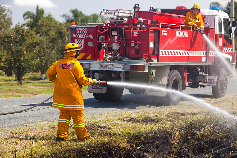 CFA fire fighters tackle a roadside fire probably started by a motorist throwing a cigarette out of the window, near Shepperton, Victoria, Australia, Pacific