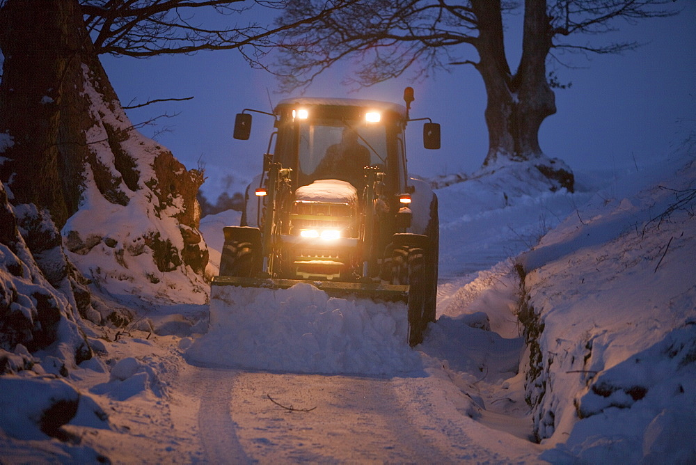 A farmer clearing snow from a lane near Ambleside, Lake District, Cumbria, England, United Kingdom, Europe