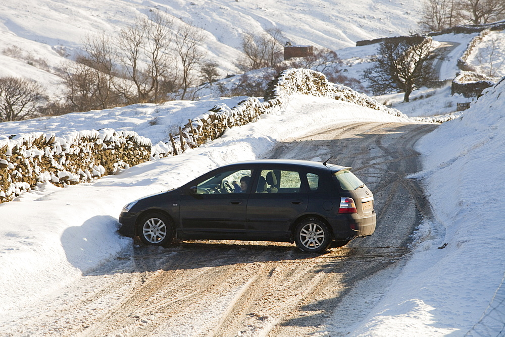 A car that skidded on ice on the Kirkstone Pass road above Windermere after it was blocked by spindrift and wind blown snow, Lake District, Cumbria, England, United Kingdom, Europe